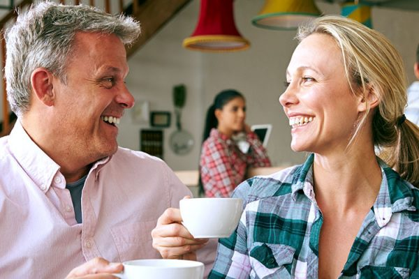 """A man and woman in a coffee shop, sitting down and looking at each other while smiling and """"cheers""""-ing their coffee mugs"""