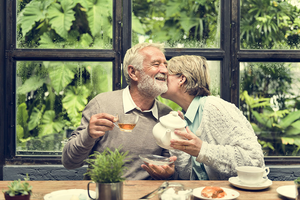 Older couple enjoying hot tea and pastries during a rainy day, and the wife is whispering in her husband's ear